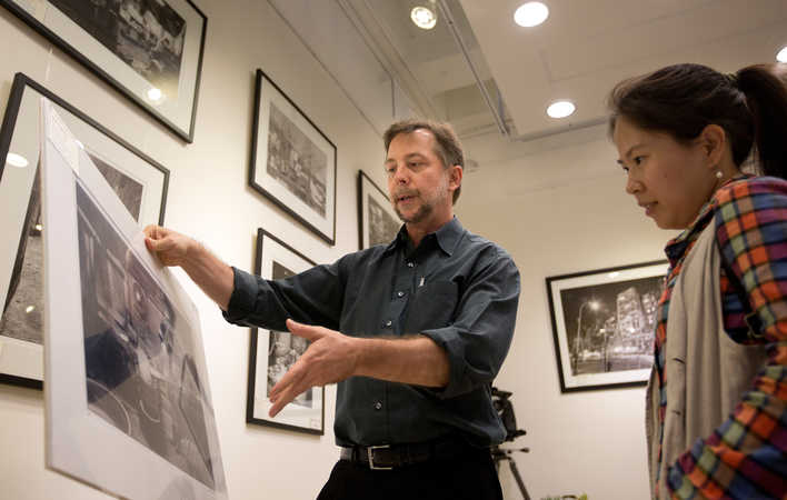 David Hartung shows a visitor a print from his Walled City photography exhibition in Hong Kong